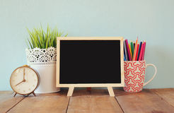 Blackboard, stack of colorful pencils and clock. back to school concept Royalty Free Stock Images