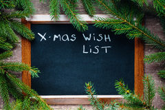 Blackboard surrounded by fir branches with text xmas wish list. Blackboard surrounded by fir branches with text Stock Photos