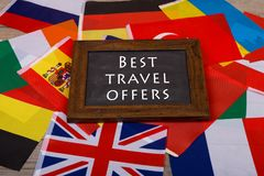 Blackboard with text & x22;Best travel offers& x22;, flags of different countries on wooden background. Travel time - blackboard with text & x22;Best travel Stock Photos