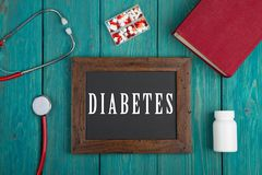 Blackboard with text & x22;Diabetes& x22;, stethoscope, pills and book on blue wooden background stock photo