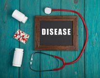 Blackboard with text & x22;Disease& x22;, book, pills and stethoscope on blue wooden background stock photo