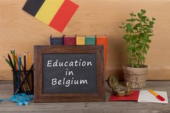 """Blackboard with text """"Education in Belgium"""", flag of the Belgium, books, chancellery on table. Education concept - blackboard with text """"Education royalty free stock photo"""