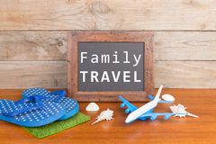 blackboard with text & x22;Family travel& x22;, plane, flip flops, seashells on brown wooden background royalty free stock photography