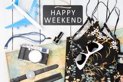 blackboard with text & x22;HAPPY WEEKEND& x22;, plane, map, sunglasses, watch, camera Royalty Free Stock Photos