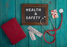 Blackboard with text & x22;Health & Safety& x22;, book, pills and stethoscope on blue wooden background royalty free stock photo