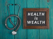 Blackboard with text & x22;Health is wealth& x22; and stethoscope on blue wooden background. Medecine concept - Blackboard with text & x22;Health is wealth& x22 Royalty Free Stock Photos