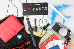 blackboard with text & x22;I love Paris& x22;, plane, map, passport, money, watch, camera, notepad, sunglasses, wallet stock image