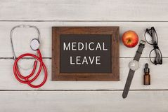 blackboard with text & x22;Medical leave& x22;, eyeglasses, watch and stethoscope royalty free stock photography