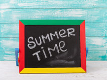 Blackboard with text it's summer time on wooden deck Royalty Free Stock Image