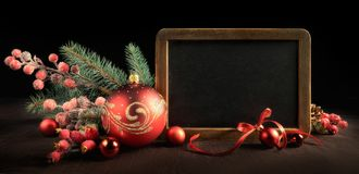 Blackboard with text space and Christmas decorations on black ba. Blackboard with text space surrounded by Christmas decorations on black background. Panoramic Stock Photo