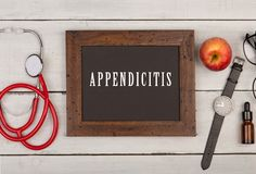 blackboard with text & x22;Appendicitis& x22;, stethoscope and watch