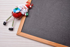 Blackboard on wood background with santa claus and copy space fo Stock Photos