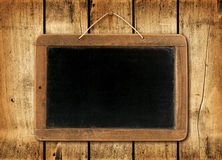 Blackboard on a wood wall background Stock Photography