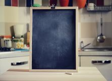 Blackboard on wooden table on kitchen  background. Empty blackboard on wooden table on kitchen  background Royalty Free Stock Photo