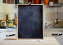 Blackboard on wooden table on kitchen  background. Empty blackboard on wooden table on kitchen  background Royalty Free Stock Images