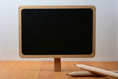 Blackboard on wooden table with pencil Royalty Free Stock Image