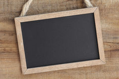 Blackboard on wooden wall Royalty Free Stock Photos