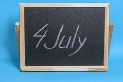 Blackboard with the word chalked 4th of july on blue background royalty free stock photo