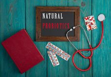 Blackboard with word & x22;Natural probiotics& x22;, stethoscope, book, pills on blue wooden background stock images