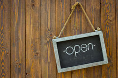 Blackboard with the word open with rope on wooden door of a coff Royalty Free Stock Photo