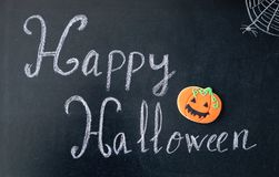 Happy Halloween. Blackboard with the words `Happy Halloween` and a pumpkin cookie Royalty Free Stock Photo