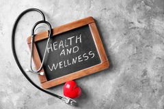 Blackboard with words \'Health and wellness\' and medical stethoscope on grey background stock photography