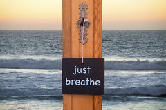 Blackboard with words Just Breathe in front of ocean. Small blackboard with the words Just Breathe hanging on key in front of the ocean Royalty Free Stock Images