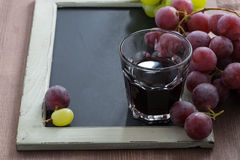 Blackboard for writing, glass of red wine and grapes Stock Photos