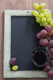 Blackboard for writing, glass of red wine and grapes, top view Stock Images