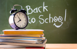 The blackboard is written Back to school. Books and clocks. Conc Royalty Free Stock Images