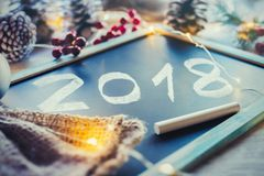 Blackboard with 2018 written in white chalk. And some Christmas decorations and lights around it Royalty Free Stock Photos