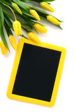 Blackboard with yellow tulips Royalty Free Stock Images