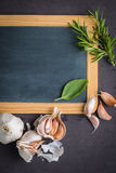 Blackboard for your text, fresh garden herbs on stone table. Bas Royalty Free Stock Image