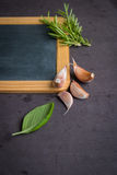 Blackboard for your text, fresh garden herbs on stone table. Bas Royalty Free Stock Images