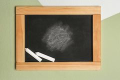Blackboard z kredowym obwieszeniem na kolor ścianie Obraz Royalty Free