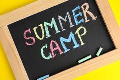 Blackboard z słowami obóz letni i kolorowa kreda na żółtym tle fotografia royalty free