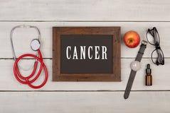 Blackboard z tekstem & x22; Cancer& x22; , zegarek, eyeglasses i stetoskop, zdjęcia royalty free