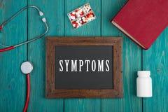 Blackboard z tekstem & x22; Symptoms& x22; , książka, pigułki i stetoskop na błękitnym drewnianym tle, obraz stock