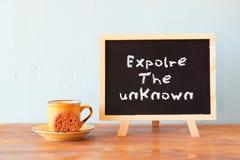Blackboard z zwrotem bada nieznane obok filiżanki kawy i ciastka obraz royalty free