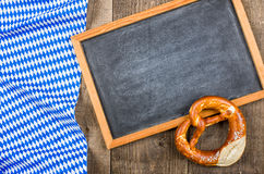 Blackboardand a pretzel with a bavarian diamond pattern Stock Images