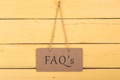 Blackboards with inscription `FAQ`s`. On yellow wooden background stock images