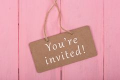 Blackboards with text `You`re invited`. On pink wooden background royalty free stock image