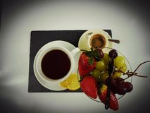 Blackcoffee blackbackground eat fruits tea lemon. Drink hot strawberry grapes whitegrapes blackplate teaspoon Royalty Free Stock Images