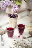 Blackcurrant homemade liquor with lilac flowers. Wooden background Royalty Free Stock Image