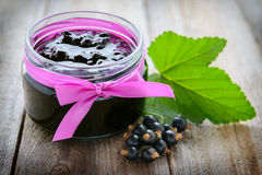 Blackcurrant jam in jar on wooden table Royalty Free Stock Photo
