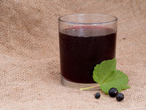 Blackcurrant juice in glass. Hessian behind. Royalty Free Stock Images