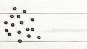Blackcurrants van de tafelbladmening verspreidden zich op witte raad, ruimte voor tekst op rechterkant stock afbeeldingen