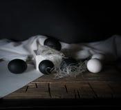 BlackEaster Noche de Pascua Huevos blancos y negros, plumas en una tabla de madera vendimia Fondo oscuro Foto de archivo