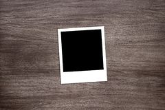 Blackened instant photo print template on wooden background Stock Photo