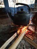 Blackened kettle log fire native cooking flames wood fire. Native cooking with old blackened kettle over log fire with flames smoke and wood. Typical for areas royalty free stock images